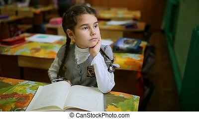 Girl schoolgirl sitting at a desk by the window and looking...