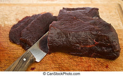 Raw whale meat - Cutting raw whale meat into thin slices on...