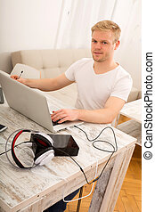 Working at home - A young caucasian man working in his home...