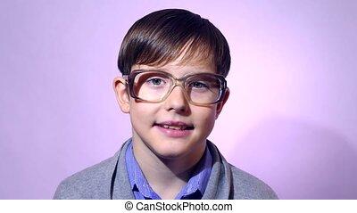 Portrait boy teenager schoolboy nerd glasses on purple...