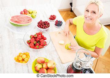 Mature woman preparing a smoothie - A beautiful mature woman...