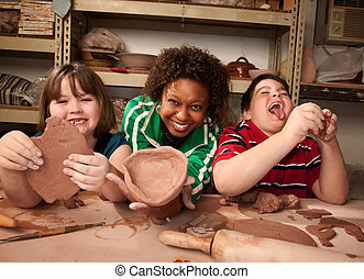 Teacher and young students in clay studio