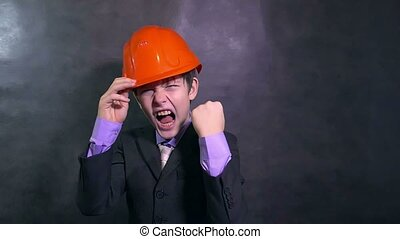 boy angry teenage architect builder in helmet swears yells...