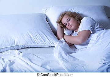 Young woman sleeping in Bed at night - A young plus size...