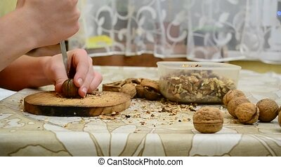 Teenager cracking walnuts with a kn - Agile teenager...