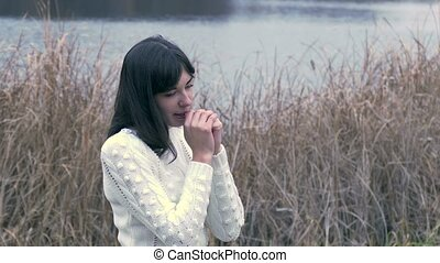 woman girl cold rubs his hands in white jacket from grass...