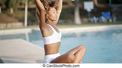 Woman Meditating By The Swimming Pool