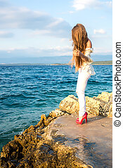 Beautiful young woman looking at the ocean - A beautiful...