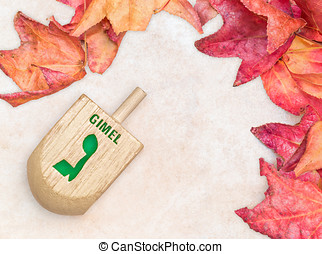 Chanukah wooden dreidel and autumn leaves on textured light...