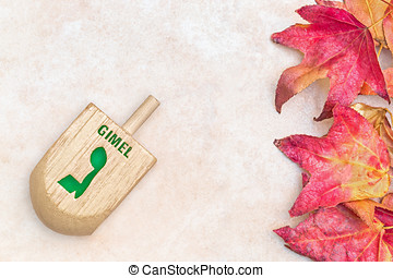 Chanukah wooden dreidel and fall leaves on textured light...