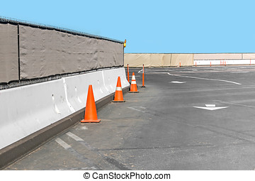Construction fence and concrete wall, orange traffic cones...