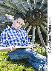 young cowboy lying beside a wagon wheel