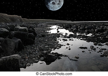 full moon over rocky beach - grey boulders and rocks on...