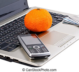 mobile phone with mandarine on gray laptop