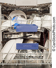 Utensils in dishwasher, washed cups and plates