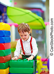 kid building blocks in kindergarten