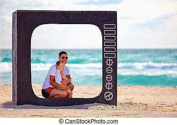 family posing in tv frame on the beach