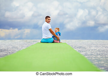 father and son sitting on the pier