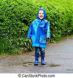 funny happy kid jumping in puddles