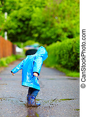 cute kid jumping in puddles