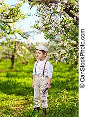 cute kid gardener in spring apple garden