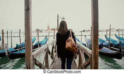 Woman walking on dock at Grand Canal Venice, Italy - Woman...