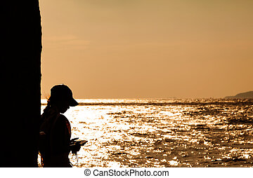 Silhouette of the young women use mobile phone near the beach., with beautiful light of sunset behind.