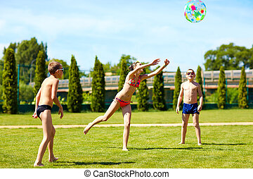 group of teenage kids playing with ball on summer lawn