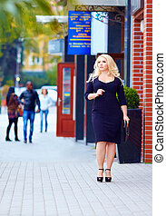 beautiful plus size woman walking the city street