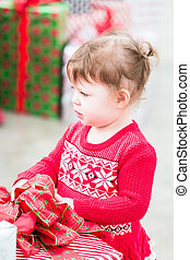 Toddler - Cute toddler girl looking at Christmas presents