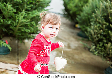 Toddler - Cute toddler girl looking for Christmas tree