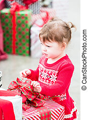Toddler - Cute toddler girl looking at Christmas presents.