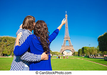 Young happy couple on the Champ de Mars in Paris background...