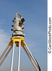 Theodolite - A surveyors equipment setup with blue sky as...