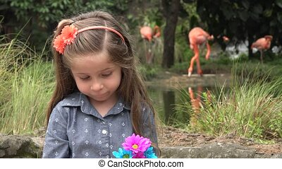 Female Toddler with Flowers Near Flamingos
