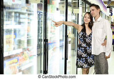 grocery store - youg couple looking at food near freezer in...
