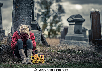 Lonely Sad Young Woman in Mourning in front of a Gravestone...