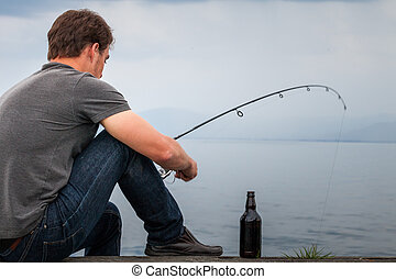 Young Fisherman Fishing Mackerel sat on the Dock with a Beer