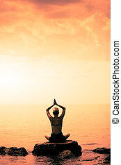 Young Woman doing Lotus Yoga Position in Front of the Ocean
