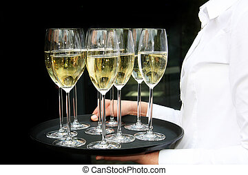 A waiter with champagne glasses on a tray. The background is...