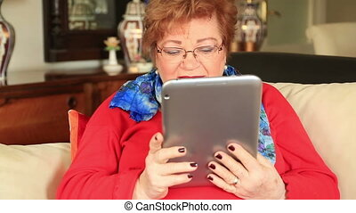 Woman using digital tablet - Senior woman sitting on a sofa...