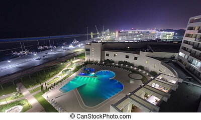 Sea beach, swimming pool and yacht in the sea at night...