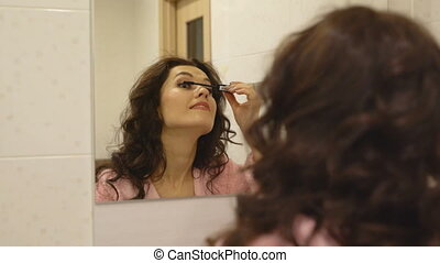 View of attractive brunette paints her eyelashes in bathroom