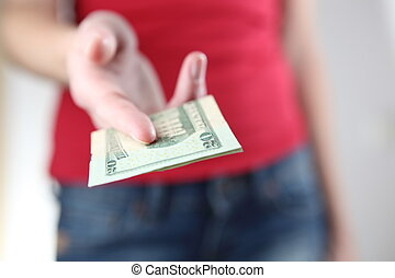 Young woman handinggiving you money 20 USD billbanknote