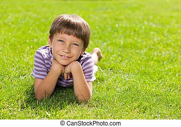 Happy little boy on the grass - A happy little boy is lying...