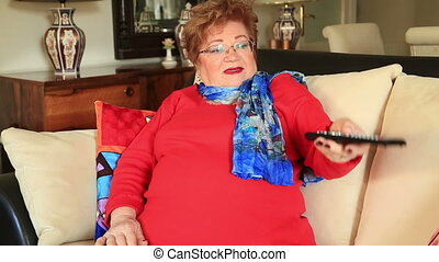 Caucasian woman watching tv - Elderly overweight woman with...