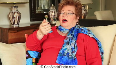 Woman using asthma inhaler - Mature woman using asthma...
