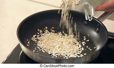 Chef is Drying Oat-Flakes on a Frying Pan