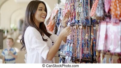 Woman Choosing Clothes At Store - Young woman choosing...