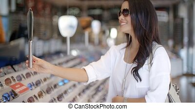 Woman In Optical Store Choosing Eyeglasses - Young woman...